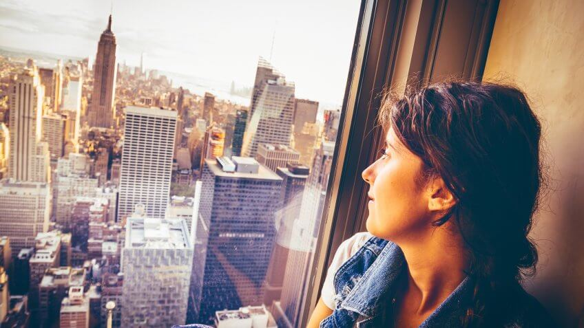 Young woman sitting near a window in New York.