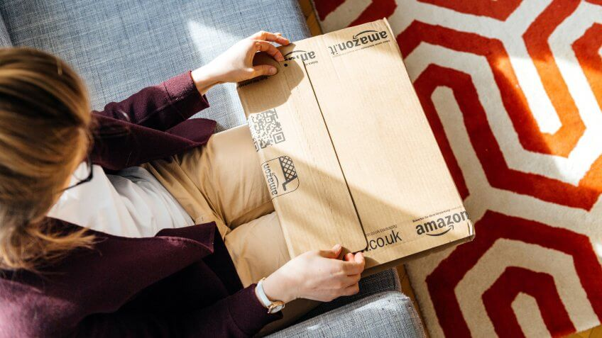 PARIS, FRANCE - APR 24 2017: Living room view from above of woman unpacking unboxing Amazon cardboard box logotype printed cardboard box side.