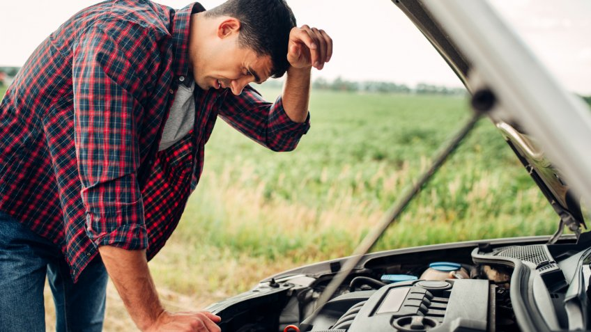 Tired man tries to repair a broken car.