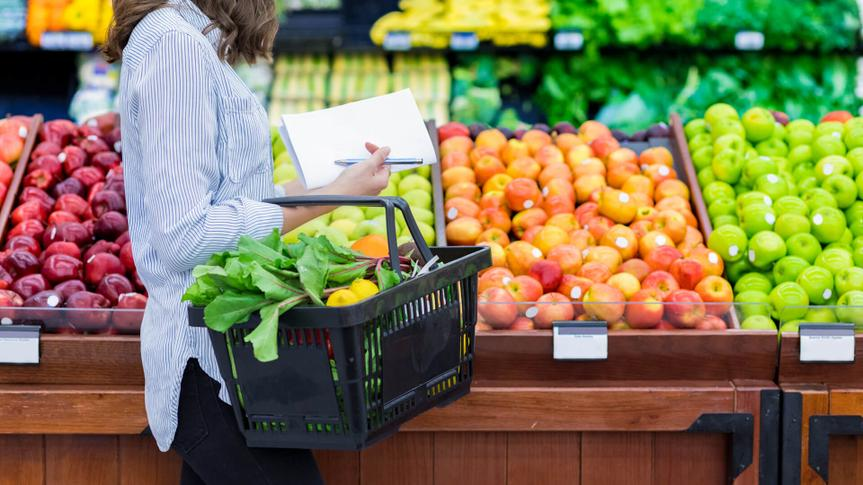 woman carries a shopping basket filled with fresh produce