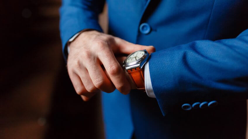 Closeup with businessman hands closing elegant blue suit jacket and wearing banker expensive wrist watch.