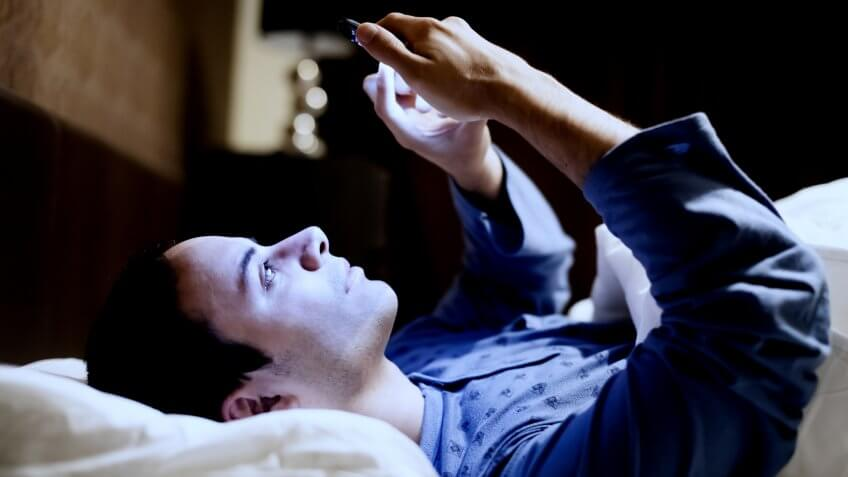 Man using his mobile phone in bed