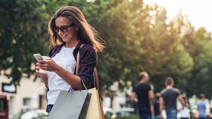 Young woman texting while enjoying a day shopping.