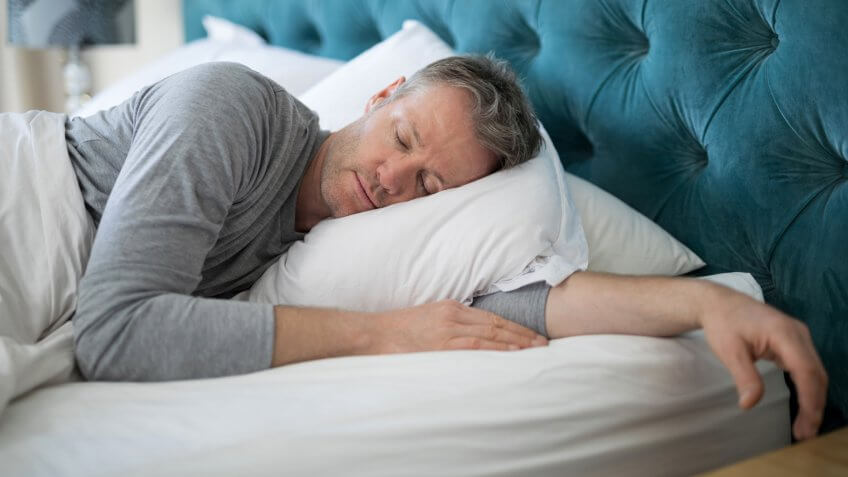 Man sleeping on bed in bedroom at home.