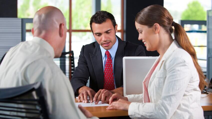 Couple signing loan documents at a bank.