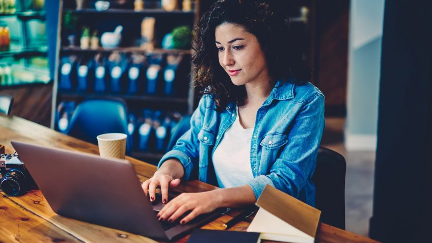Young beautiful woman dressed in stylish outfit transferring money using online banking service on laptop computer connected to wifi.