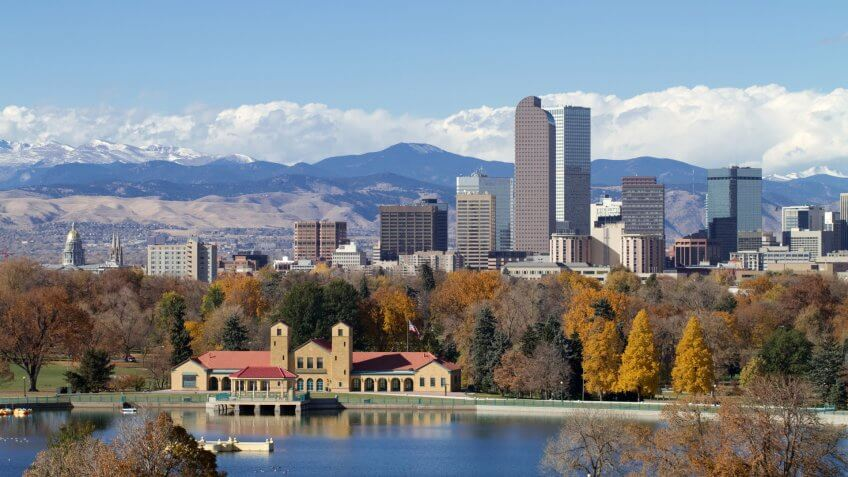 Scenic of Denver Colorado skyline, with Rocky Mountains in the background and City Park Lake in the