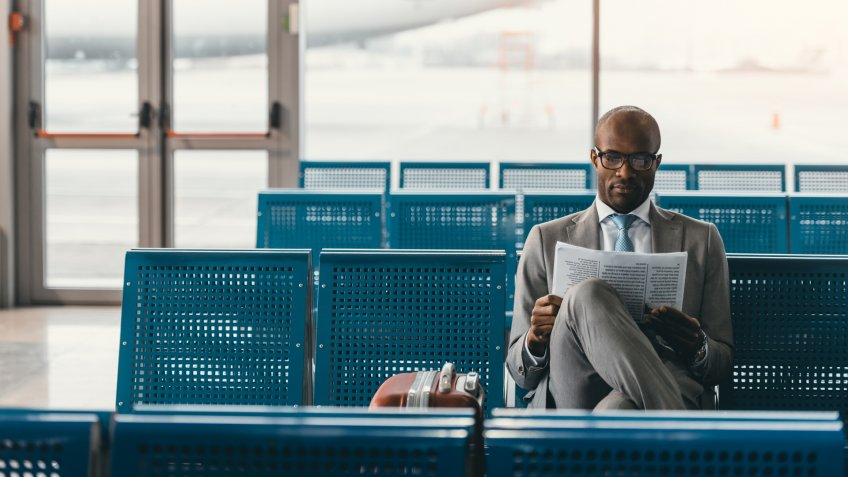businessman reading newspaper at airport lobby