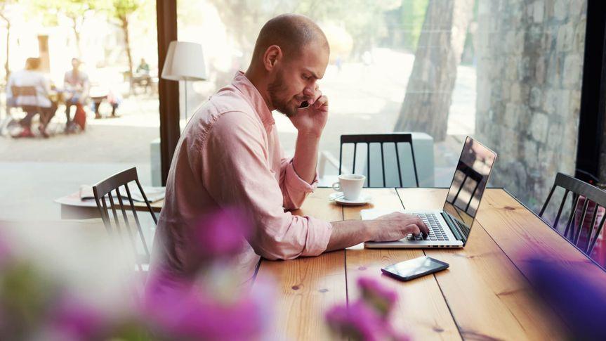 Man working on laptop at cafe
