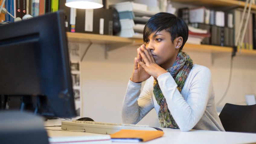 Shot of an young woman sitting and thinking at her desk in startup office.