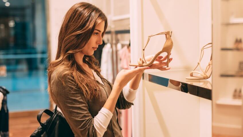 Woman looking at high heels in a clothing store.