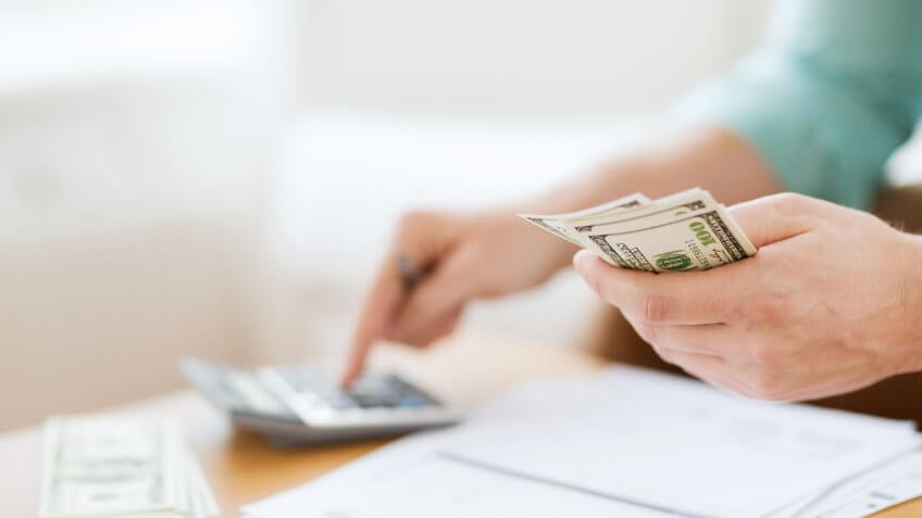 savings, finances, economy and home concept - close up of man with calculator counting money and making notes at home.
