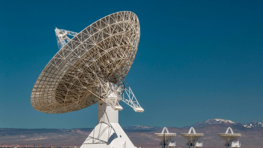 A huge satellite dish with three small satellite dishes located at the Owens Valley Radio Observatory in the Owens Valley in California.