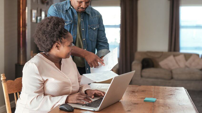 Smiling African couple paying bills and doing their online banking with a laptop at their kitchen table at home.