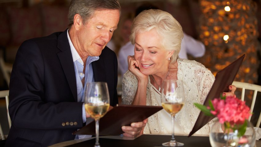 Senior Couple Choosing From Menu In Restaurant.