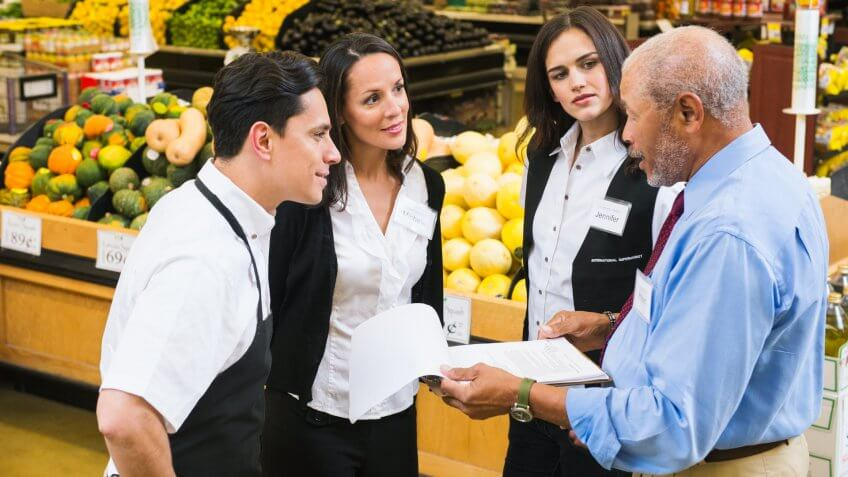 Businessman and workers talking in grocery store.