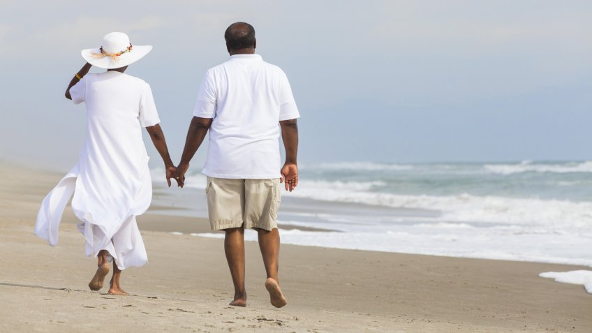 Happy romantic senior African American man and woman couple walking holding hands on a deserted tropical beach.
