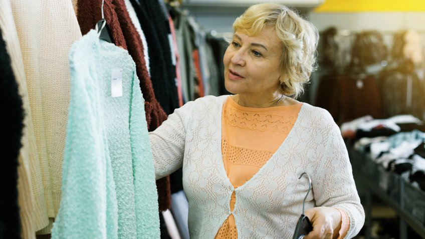 mature woman buyer choosing color cardigan in the dress shop indoors.