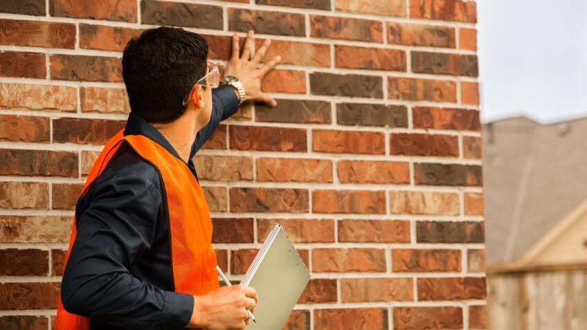 inspector examines residential home exterior