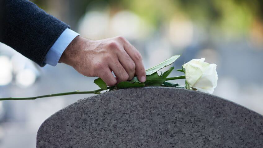 man placing a white rose on a grave