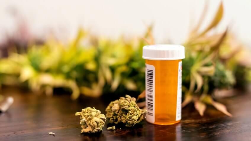 Marijuana buds sitting next to prescription medicine bottle.