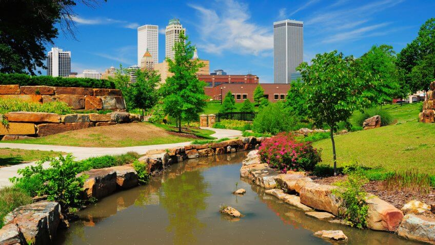 """Tulsa downtown skyline from a park with trees, grass, rocks, and a stream in the foreground."