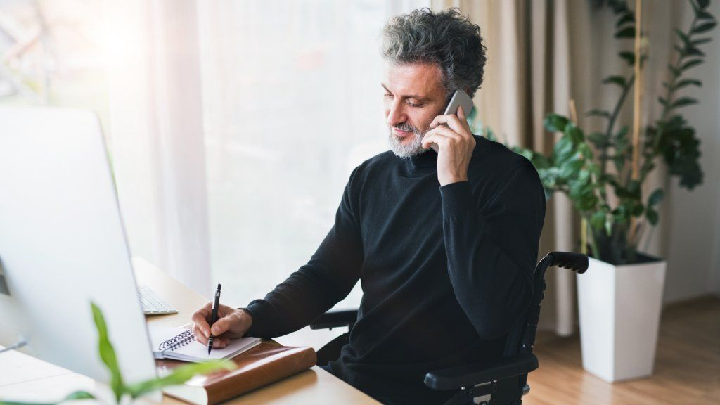 Handsome mature man in wheelchair with smartphone in home office, making a phone call.