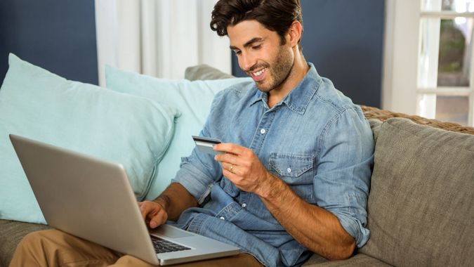 happy man on sofa looking at credit card with laptop