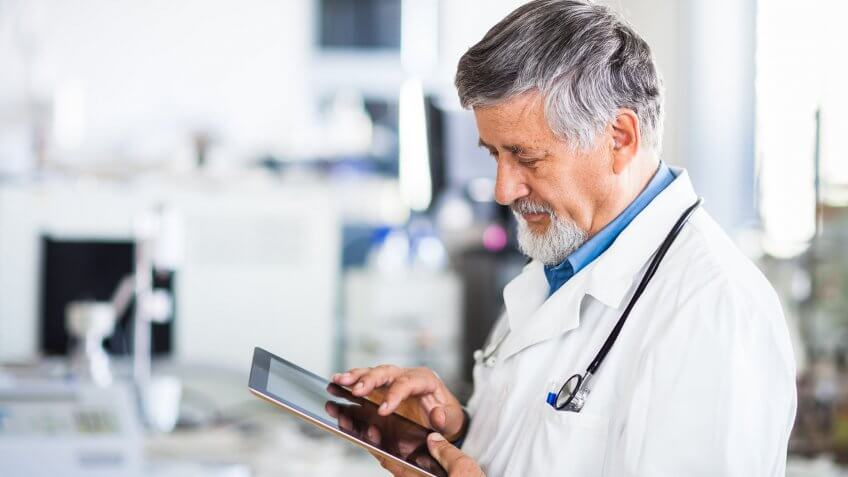 Senior doctor using his tablet computer at work.
