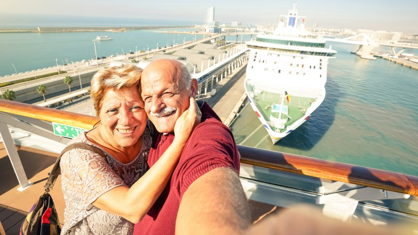 Senior happy couple taking selfie on ship on harbor background - Mediterranean cruise travel tour - Active elderly concept with retired people around the world - Bright sunny afternoon color tones.