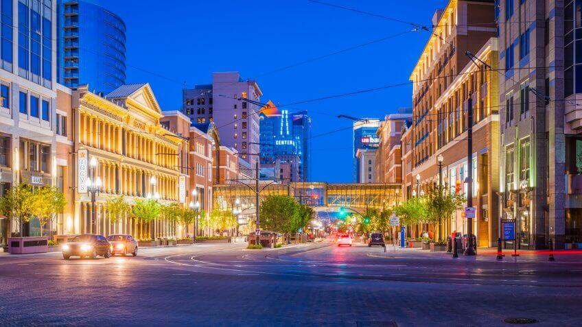 Deep blue desert dusk skies over the street lights, traffic, tram lines, illuminated store fronts and businesses of Main Street, Salt Lake City, Utah.