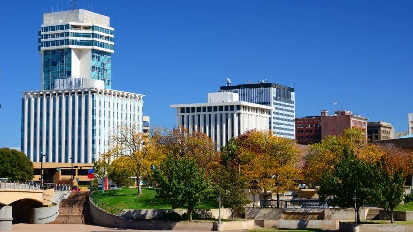 Wichita, Kansas downtown skyline during Autumn, with Autumn trees in the foreground.