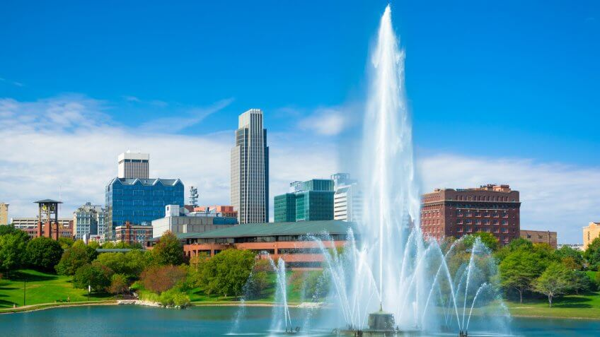 Downtown Omaha skyline in the background with a huge and elaborate fountain and a lake in the foreground (part of the Heartland of America park.