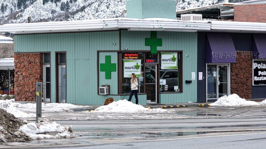 Glenwood Springs, Colorado, USA - January 6, 2016: A woman and her dog stroll past the tell-tale green crosses on a storefront in downtown Glenwood Springs that identifies it as a legal drug shop.