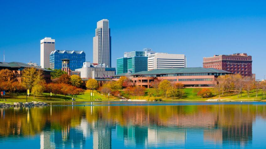 Omaha downtown skyline during Autumn, with a lake at the Heartland of America Park in the foreground.