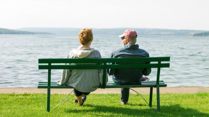 An older elderly retired couple sit on a park bench casually dressed looking at a view of a beautiful lake.