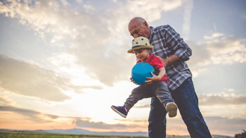 Grandfather and grandson playing with a ball and having fun together.