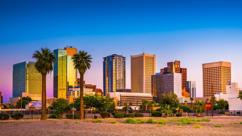 Downtown skyscrapers with palm trees and greenery in Phoenix, Arizona during sunset.