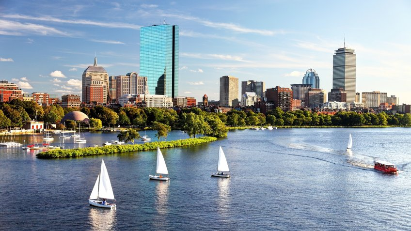 Sailboats on the Charles River with Boston's Back Bay skyline in the background.