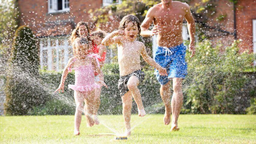 Family Running Through Garden Sprinkler