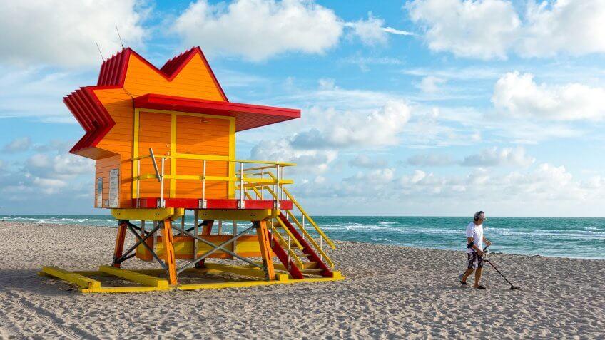 Miami, Florida, USA - December 5, 2016: Man Searching With Metal Detector Near Lifeguard Tower Miami Beach Florida.