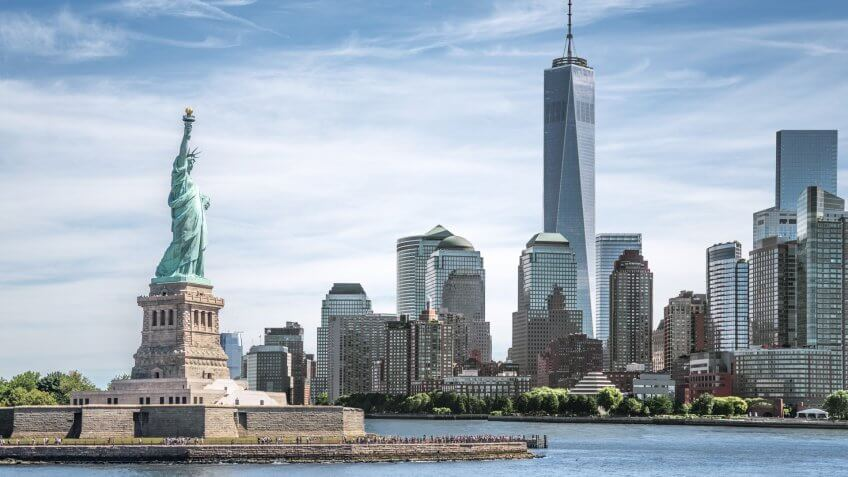 The Statue of Liberty with One World Trade Center background, Landmarks of New York City, USA.