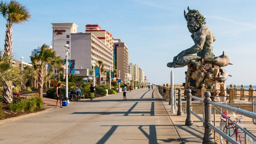 VIRGINIA BEACH, VIRGINIA - JULY 13, 2017: The King Neptune statue by sculptor Paul DiPasquale along the 3-mile long oceanfront boardwalk lined with high-rise hotels.