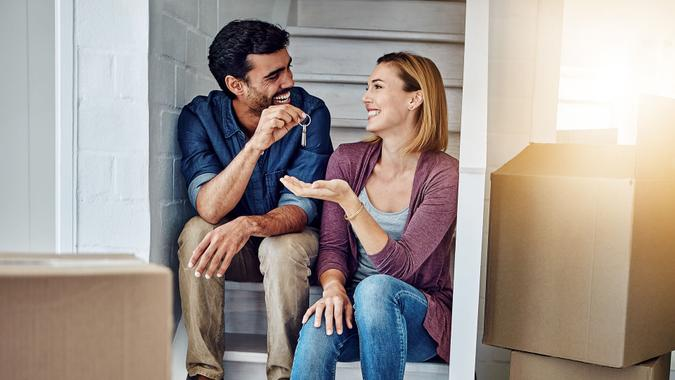 Shot of a man handing his wife the keys of their new home.