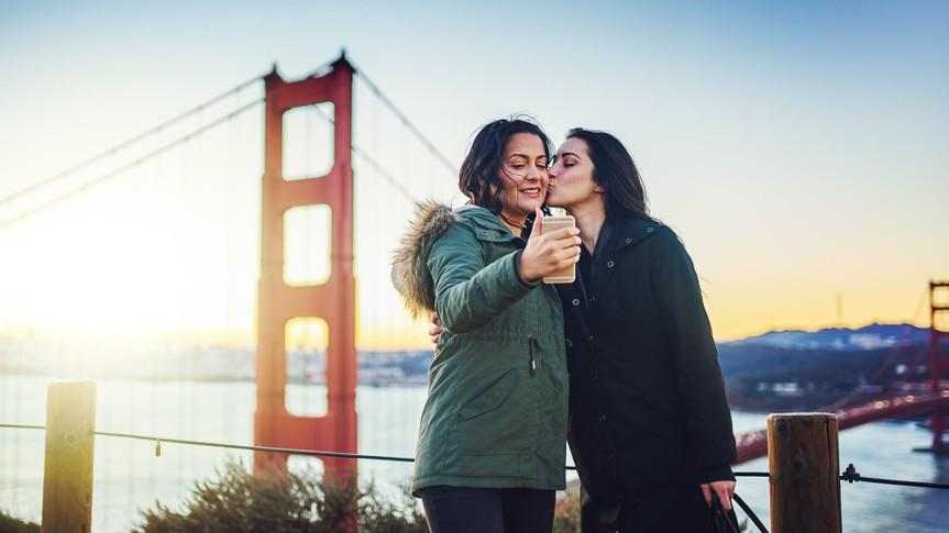 lesbian couple taking selfie at golden gate bridge together.