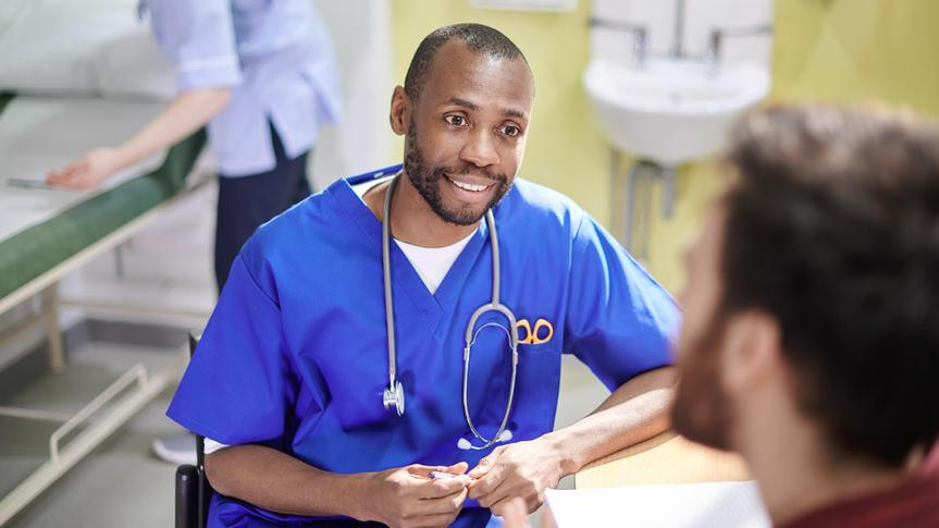 a doctor chats to a male patient in his office.