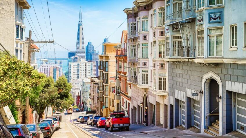 San Francisco, USA - May 10, 2016: Pacific heights street scene panoramic downhill view towards downtown with parked cars, a tramway, a man waiting in a doorway and the Transamerica pyramid in the background.
