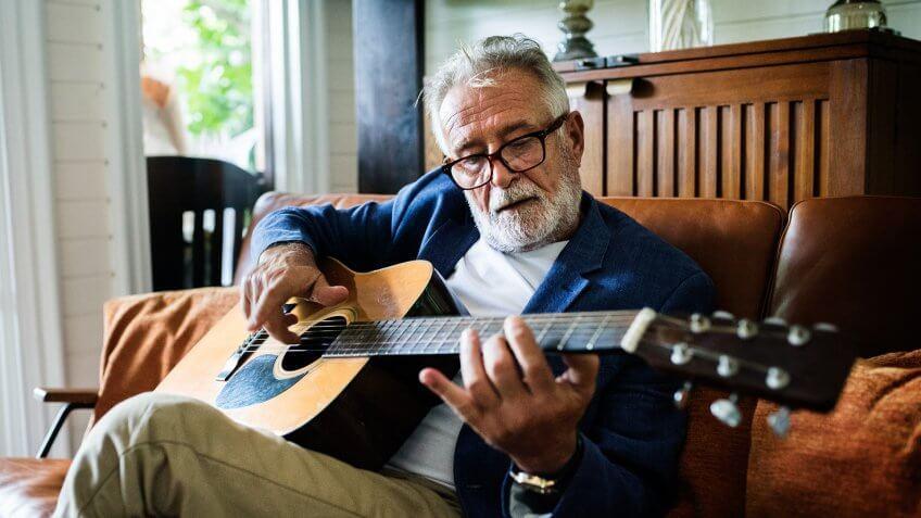 An elderly man is playing guitar.