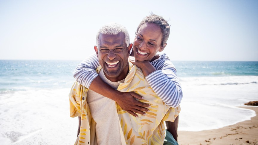 A beautiful senior black couple piggyback on the beach.