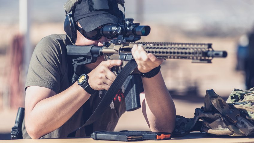 Man shooting assault style rifle at shooting range in desert resting on bench front - Image.